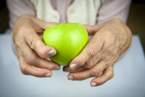 Rheumatoid arthritis hands and fruits. Apple in hand